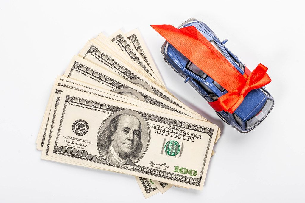 Money and metal car model with red gift ribbon on white background