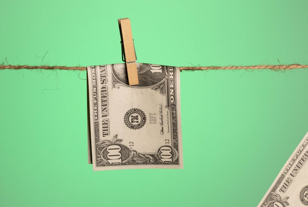 Money with wooden clothespin on clothes line with green background