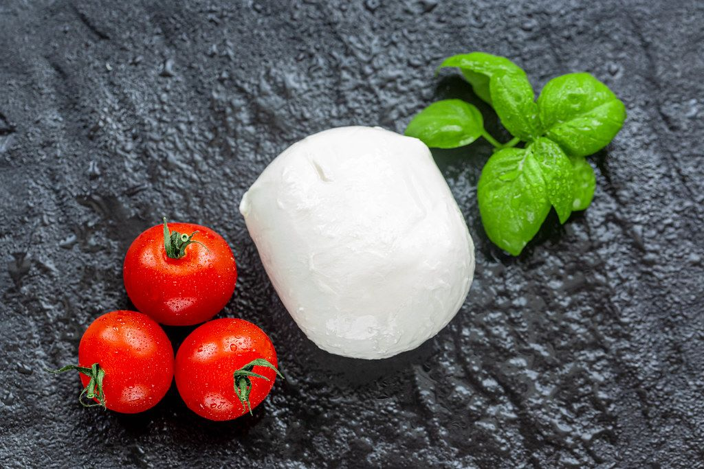 Mozzarella, cherry tomatoes and Basil leaves on black stone background