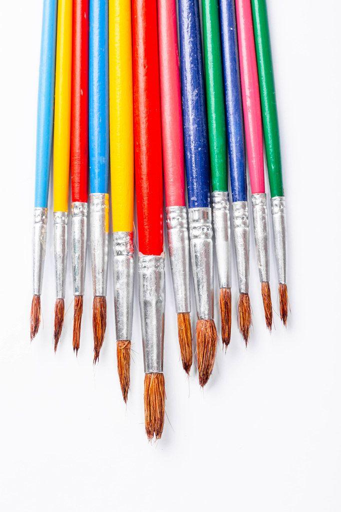 Multi-colored paint brushes on white background (Flip 2019)