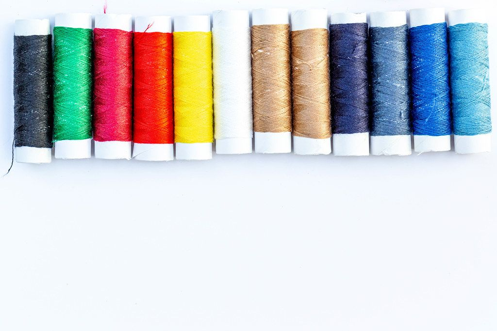 Multicolor spools of sewing thread on white background