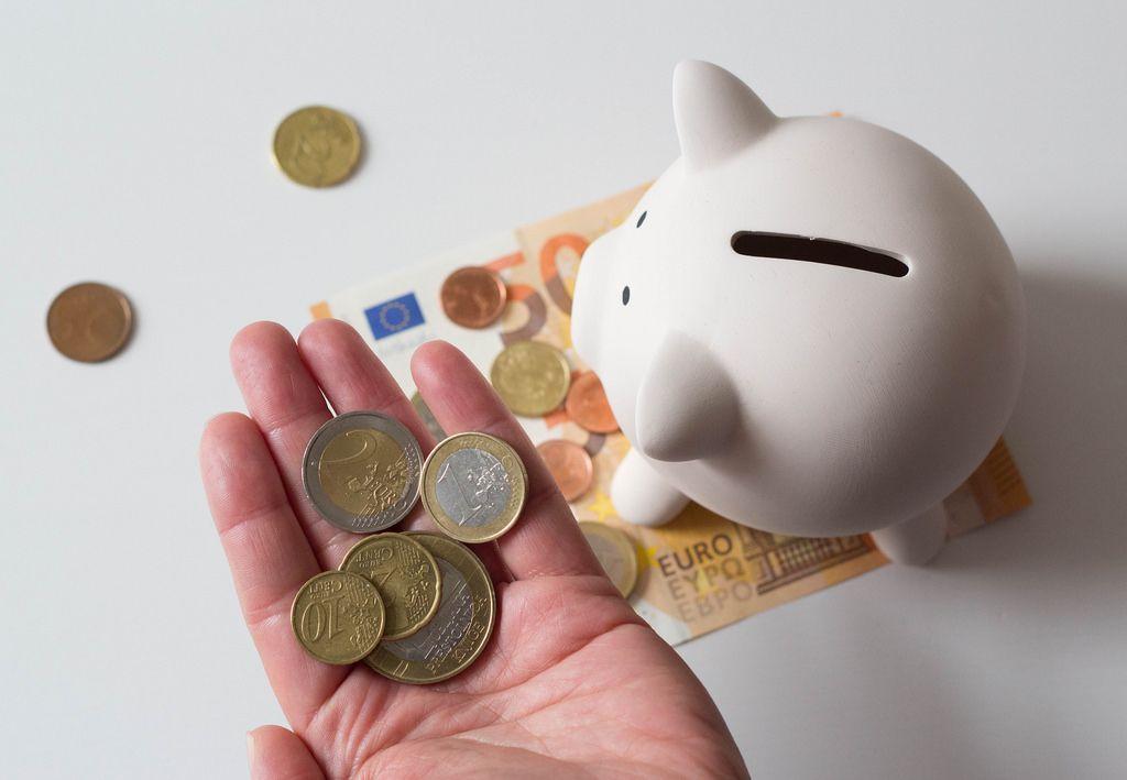 Münzen in der Hand und Sparschweinchen auf dem Tisch