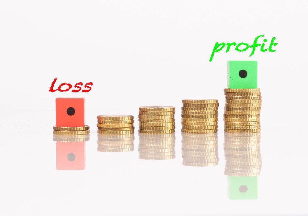Münzstapel mit Verlust - und Gewinntext