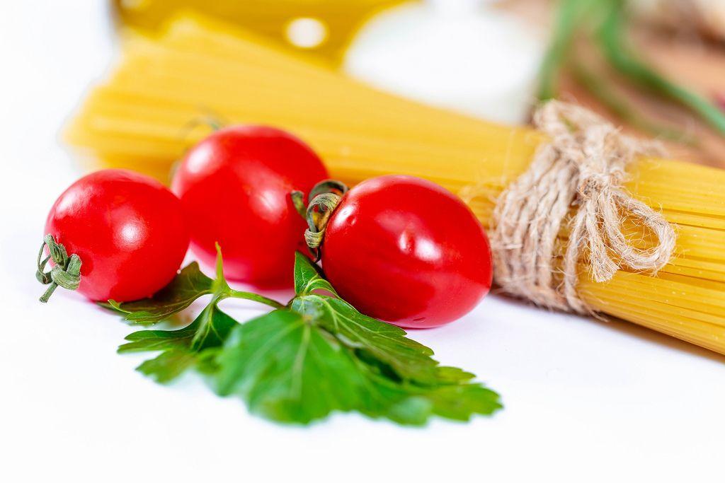 Nahaufnahme Bund Spaghetti und Cherrytomaten mit Kräutern auf weißem Untergrund