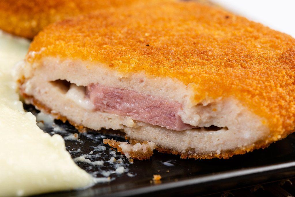 Nahaufnahme einer aufgeschnittenen Putenmedaillons, paniert und mit Schinken-Käse-Füllung