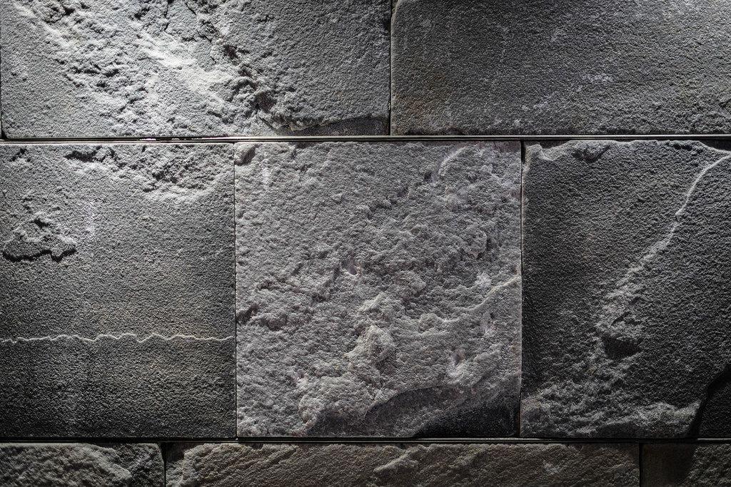 Nahaufnahme einer beleuchteten grauen Steinwand