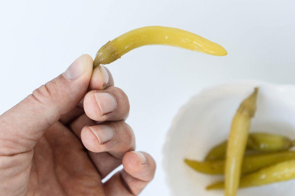 Nahaufnahme einer Hand die eine Scharfe Grüne Chilischote hält
