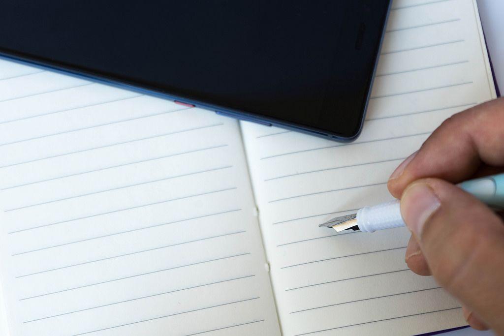 Nahaufnahme einer Hand eines Mannes der einen Schreibstift über einem Notizheft hält