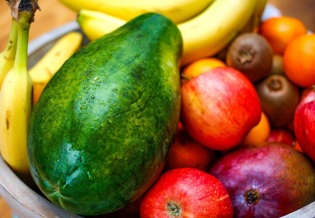 Nahaufnahme einer Papaya in einer Schüssel voll mit Früchten