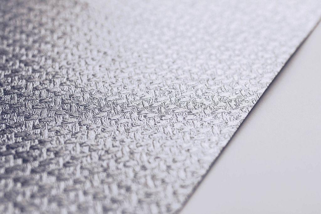 Nahaufnahme einer Papierstruktur eines silberfarbenen Dekorpapiers