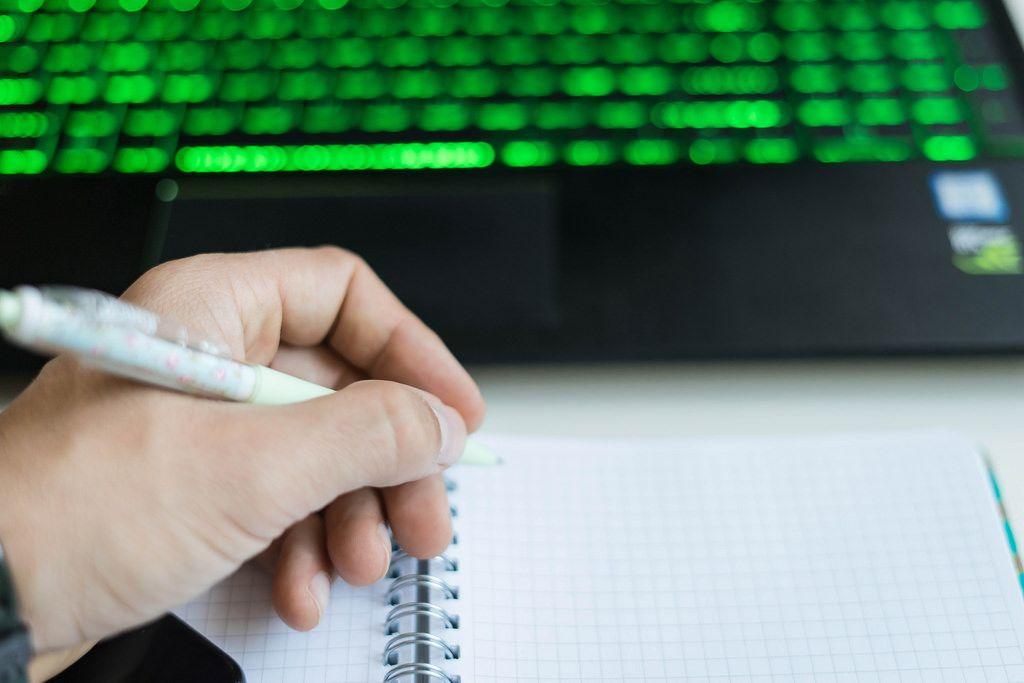 Nahaufnahme einer schreibenden Hand mit Laptop im Hintergrund