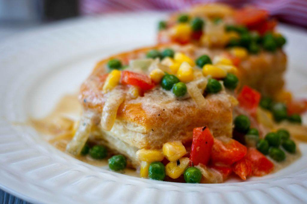 Nahaufnahme einer vegetarischen Blätterteigpastete mit Erbsen, Mais und Paprika