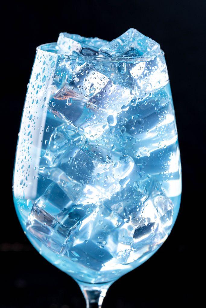 Nahaufnahme eines blauen Cocktails mit Eiswürfeln in einem Glas vor schwarzem Hintergrund