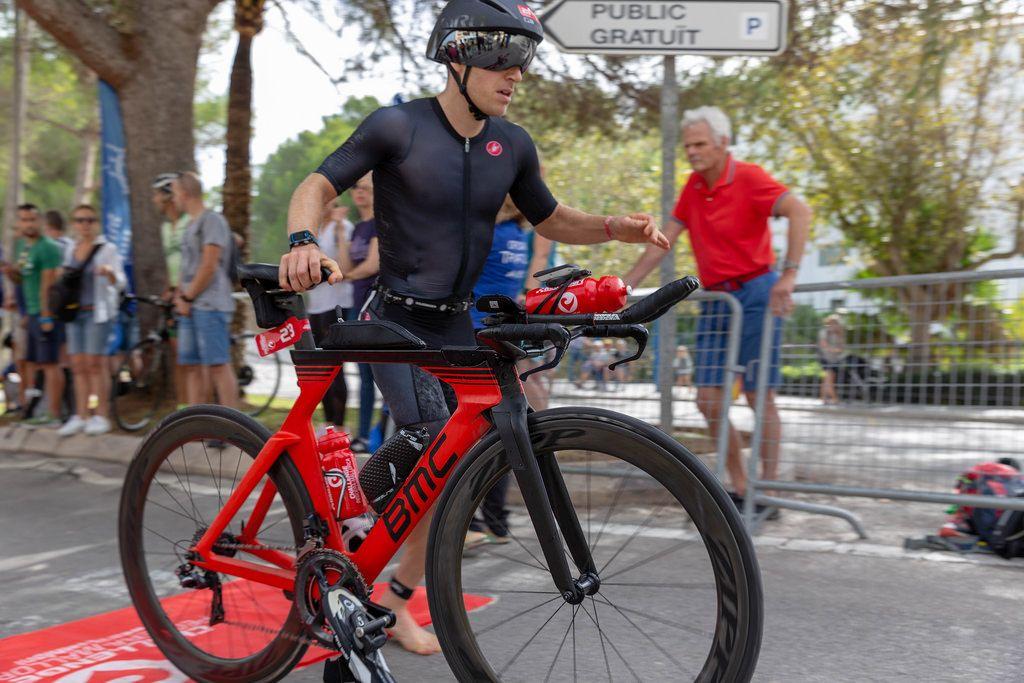 Nahaufnahme eines Mannes in schwarzer Bekleidung nimmt Anlauf um sich auf sein Rad bei einem Triathlon zu schwingen - Paguera Challenge Triathlon 2018