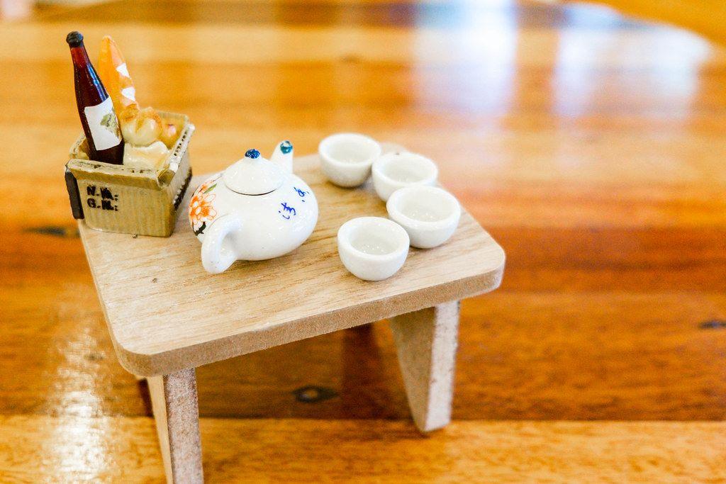 Nahaufnahme eines Miniatur-Porzellansets und kleinem Picknickkorb für ein Puppenhaus