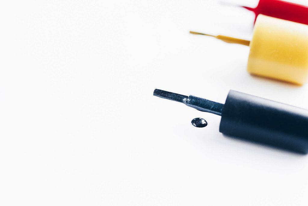 Nahaufnahme eines Nagellack-Tropfens vor weißem Hintergrund