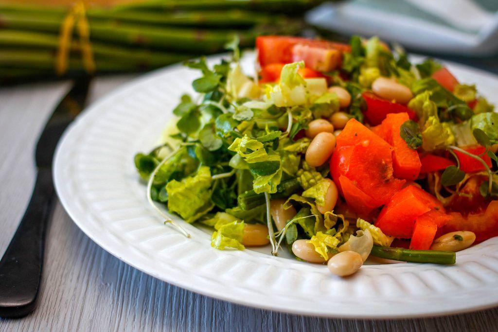 Nahaufnahme eines Salats mit Bohnen, Eisbergsalat, Tomate und Spargel