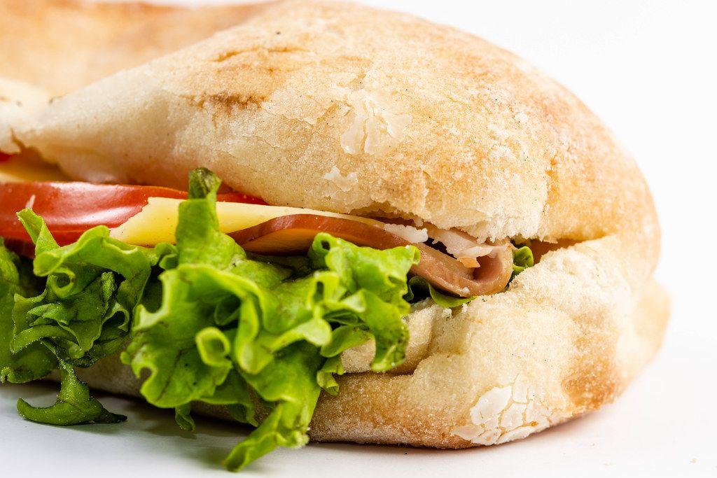 Nahaufnahme eines Sandwich mit grünem Salat, Tomaten, Schinken und Käsescheiben