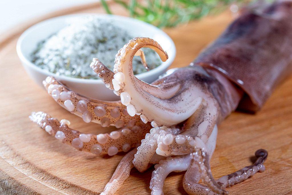 Nahaufnahme eines Tintenfischkopfs mit Tentakeln, ein einem Küchenbrett
