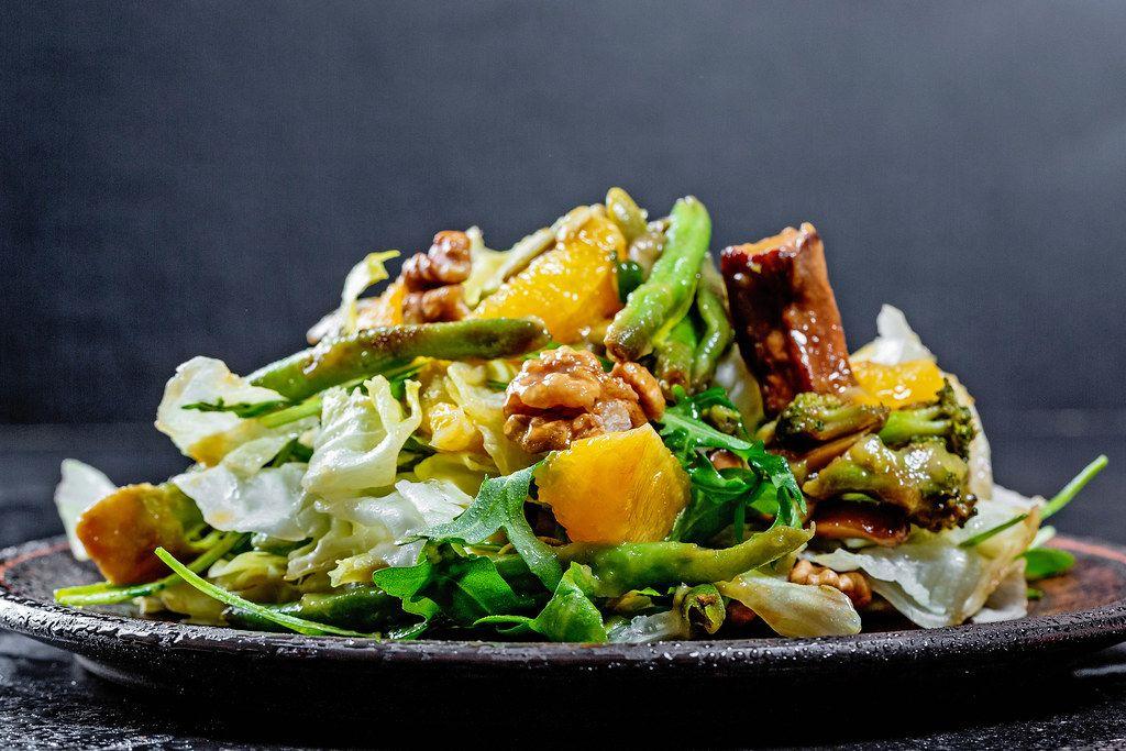 Nahaufnahme eines veganen Salats, mit Orangen, Nüssen, Brokkoli, Salatblätter und Spargel