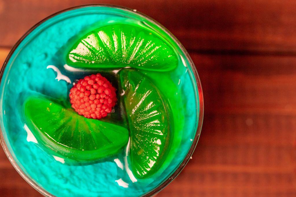Nahaufnahme eines Wackelpudding Nachtisches mit grünem Weingummi und Himbeerkern in einem Glas