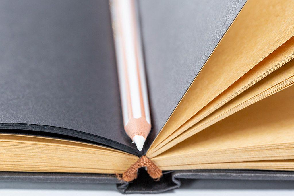 Nahaufnahme eines weißen Buntstifts auf schwarzen Papierseiten eines Notizbuchs