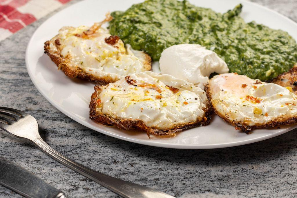 Nahaufnahme gesunde Mahlzeit aus gebratenen Eiern und Spinat auf Teller auf Steinplatte