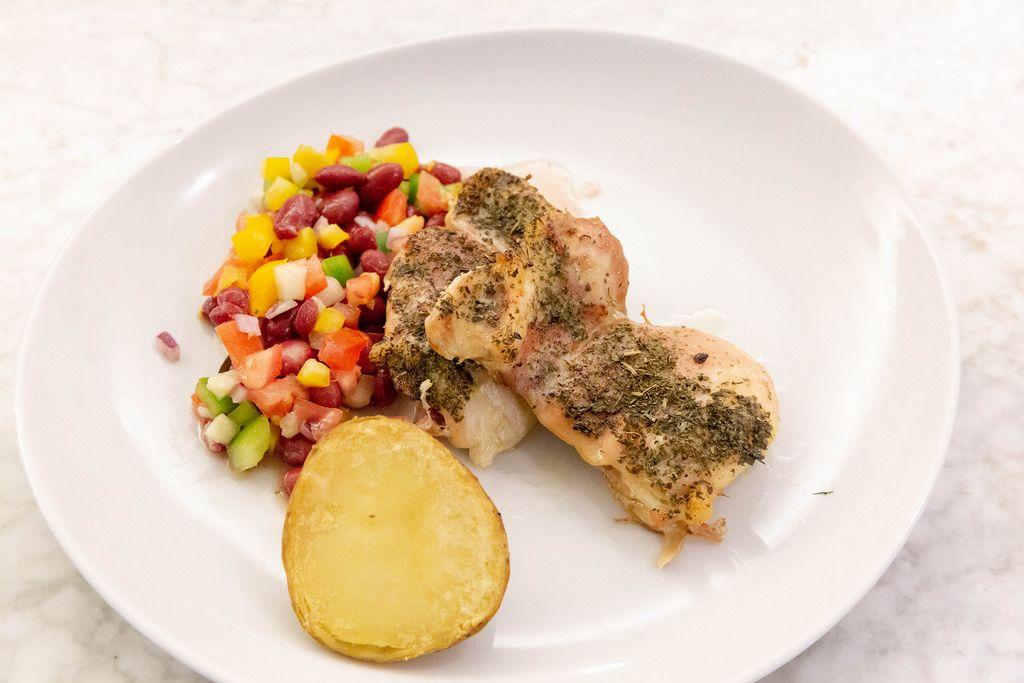 Nahaufnahme - Hähnchen in Kräutersauce mit Backkartoffel und gemischtem Salat mit Bohnen