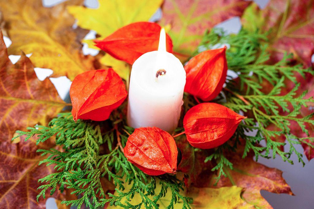 Nahaufnahme - Leuchtenede Kerze mit Physalis, Tannenzweigen und bunten Herbstblättern
