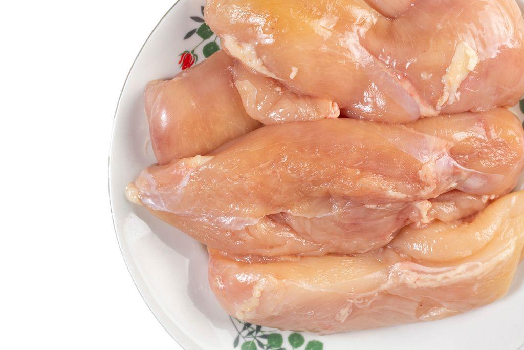 Nahaufnahme rohes, proteinreiches Hähnchenfleisch auf Teller vor weißem Hintergrund