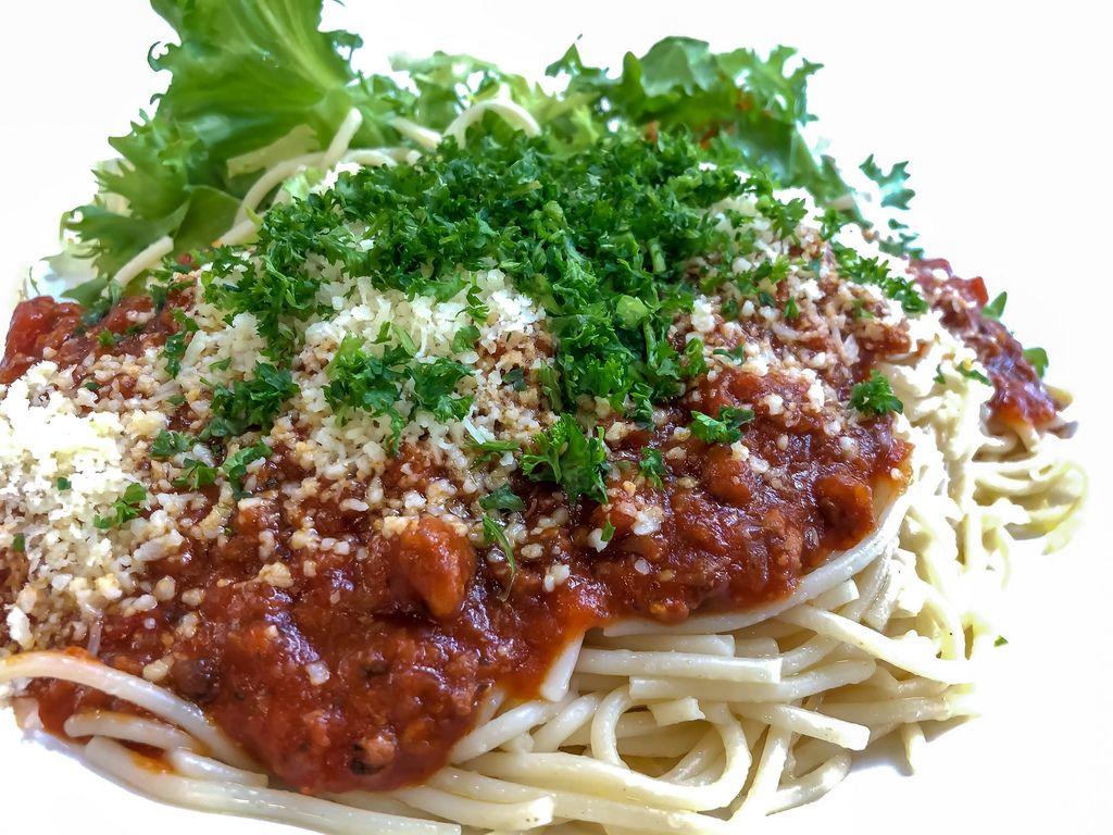 Nahaufnahme Spaghetti mit Tomatensoße, geriebenem Käse, Kräutern und Salatblättern