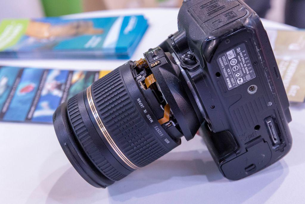 Nahaufnahme Spiegelreflexkamera mit abgebrochenem Objektiv auf weißem Tisch