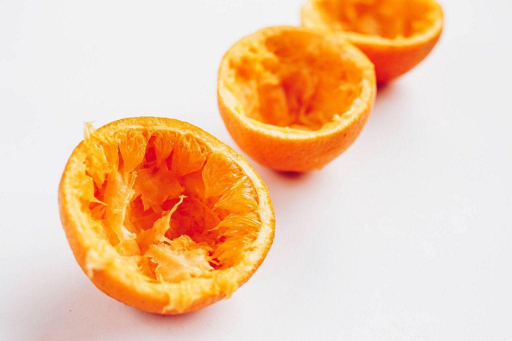Nahaufnahme von ausgepressten Orangen vor weißem Hintergrund