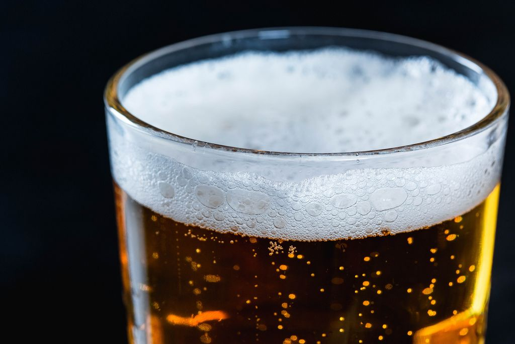 Nahaufnahme von Bier in Glas mit leichtem Bierschaum vor dunklem Hintergrund