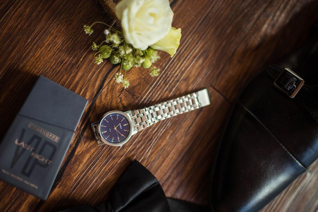 dcc38dda21 Nahaufnahme von Bräutigam-Accessoires wie Blumengesteck, Uhr und schwarze  Schuhe auf Holztisch