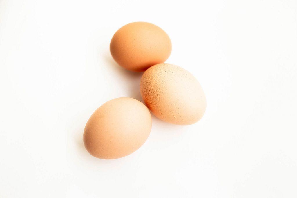 Nahaufnahme von drei Eiern mit brauner Eierschale freigestellt vor weiß
