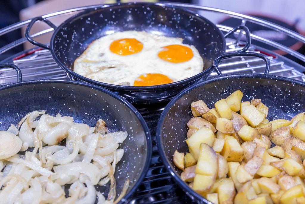 Nahaufnahme von drei Pfannen mit Bratkartoffeln, Spiegeleiern und Zwiebeln auf Metallrost