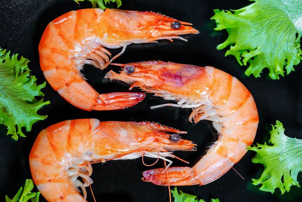 Nahaufnahme von drei ungeschälten großen Garnelen mit Salatblättern auf schwarzem Teller