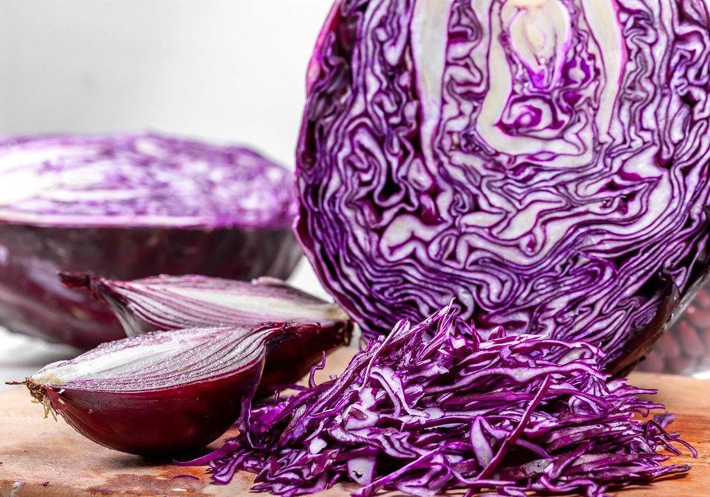 Nahaufnahme von einem Rotkohl und Zwiebeln, die geschnitten auf einem Küchenbrettchen liegen
