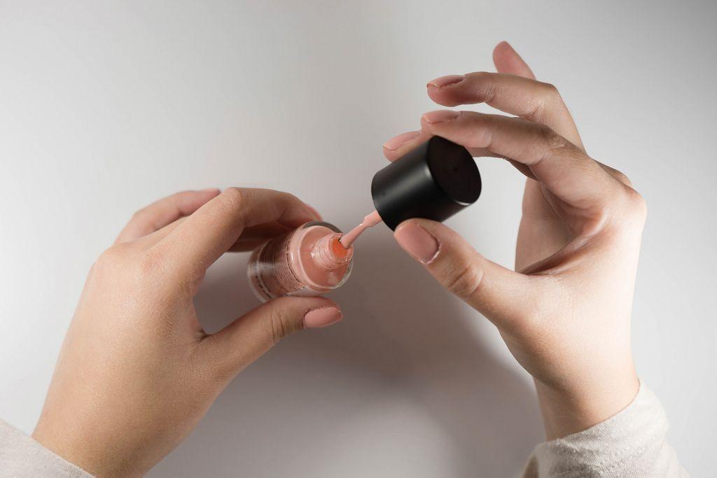 Nahaufnahme von einer Flasche rosafarbigem Nagellacks gehalten in den Händen einer Frau