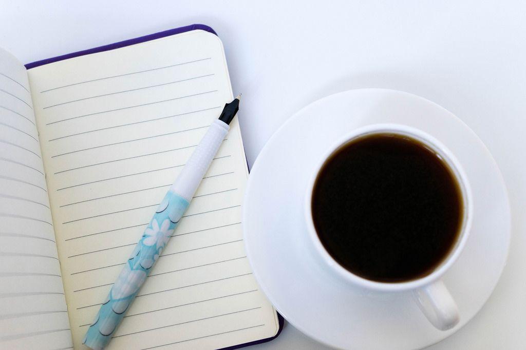 Nahaufnahme von einer Tasse Kaffee mit Notizheft und Schreibstift