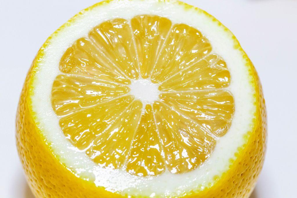 Nahaufnahme von frisch aufgeschnittener Zitrone vor weißem Hintergrund