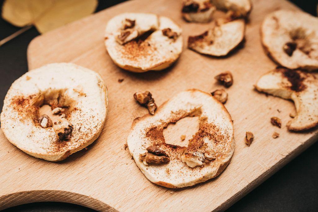 Nahaufnahme von gebackenen Äpfelscheiben mit Zimt und Walnüssen auf einem Brett