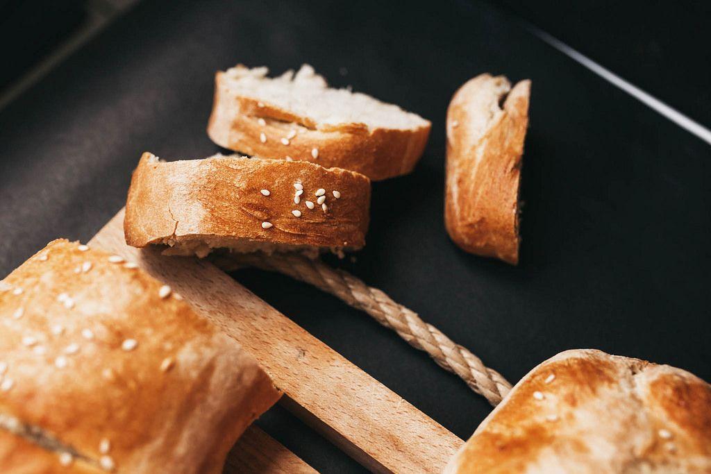 Nahaufnahme von in Scheiben geschnittenem, hausgemachtem französischem Brot mit Sesam vor dunklem Hintergrund
