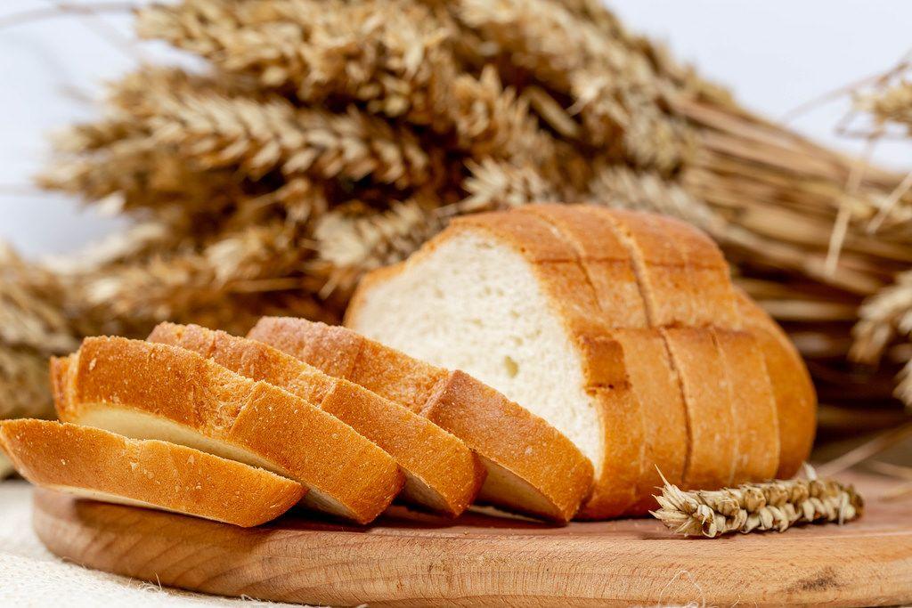 Nahaufnahme von mehreren Scheiben Weißbrot auf einem Brettchen mit Weizenähren im Hintergrund
