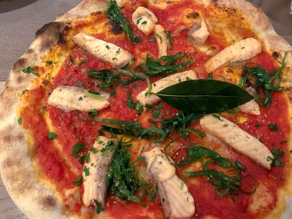 Nahaufnahme von nährstoffreicher Pizza mit Stücken aus Lachs und Algen
