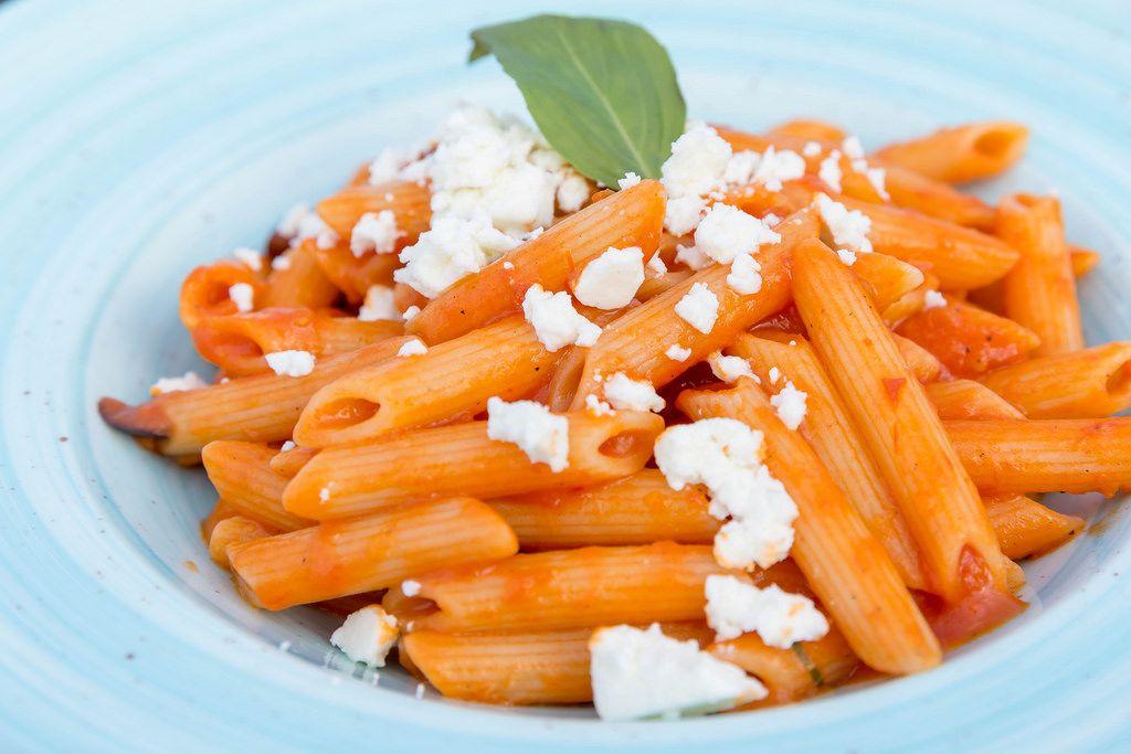 Nahaufnahme von Penne mit Tomatensoße und geriebenem Fetakäse