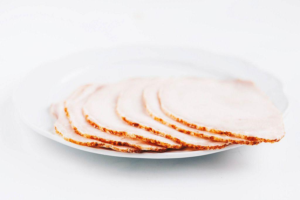 Nahaufnahme von Schinkenscheiben in weißem Teller. Weißer Hintergrund