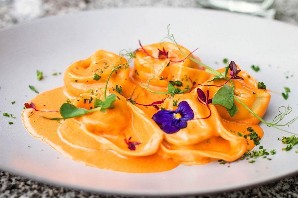 Nahaufnahme von Tortellini mit Sauce und Blumen