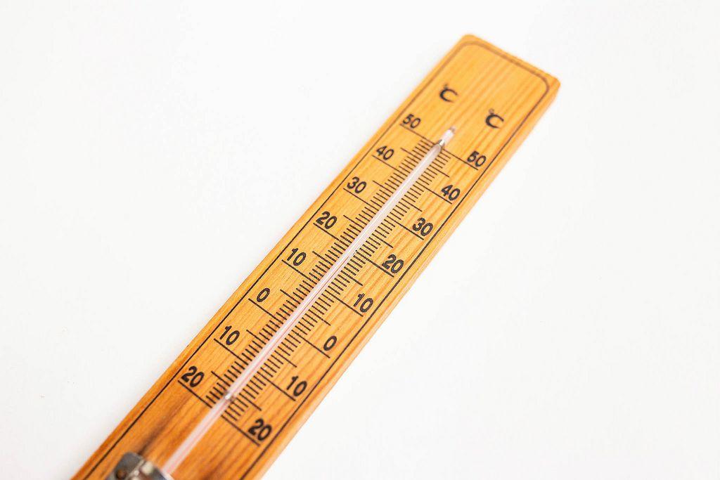 Nahaufnahme von Wand-Thermometer aus Holz vor weißem Hintergrund